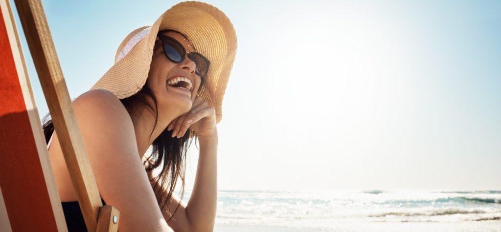 lächelnde Frau im Strohhut am Strand