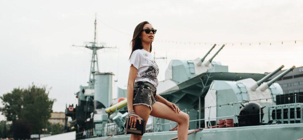 Frau in Shorts, schwarzen Pantoletten, weißem T-Shirt und mit einer kleinen Handtasche