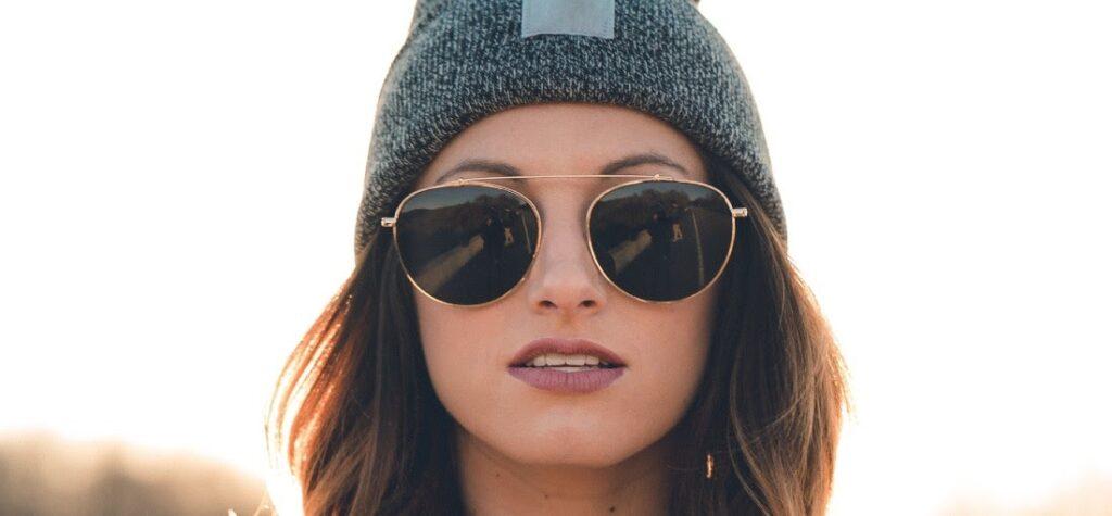 Frau in Sonnenbrillen und einer Mütze