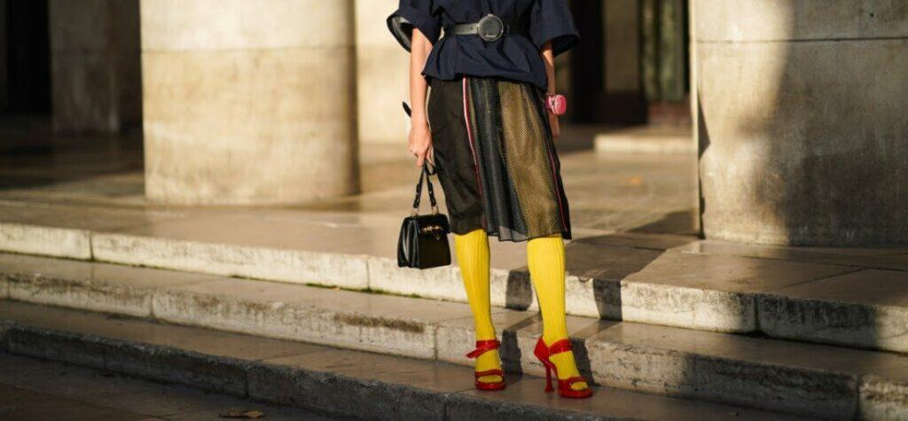 Frau in gelben Strumpfhosen und roten Sandaletten
