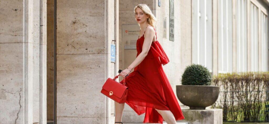 Frau im roten Kleid, in schwarzen Sandaletten und mit roter Handtasche
