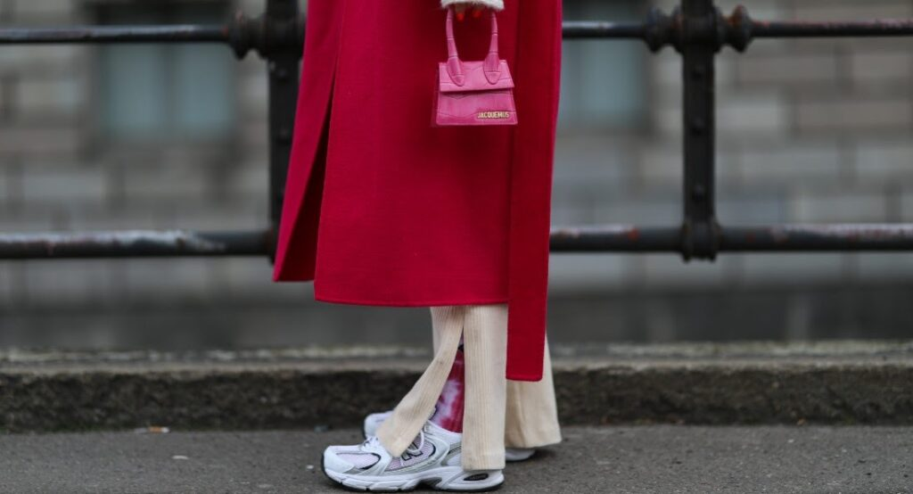 Sneakers, kleine Handtasche und roter Mantel