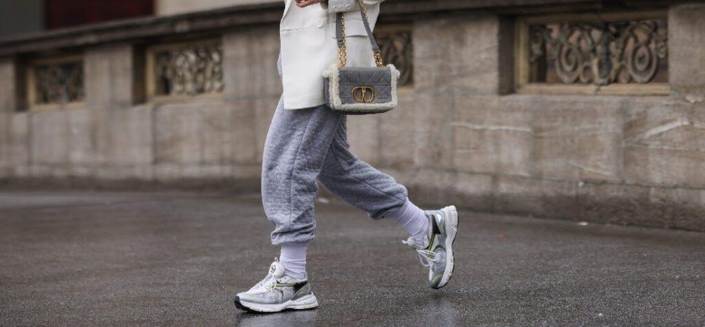 Frau in grauer Jogginghose und weißem Mantel