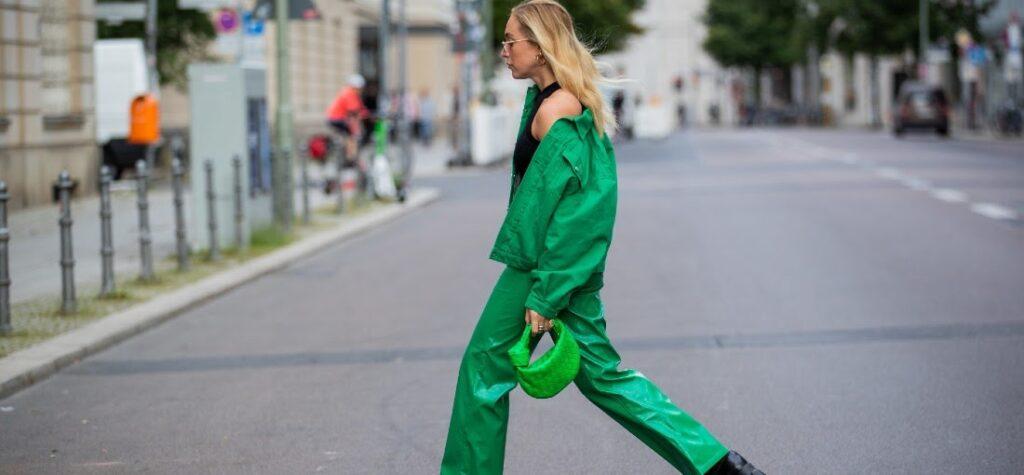 Frau in grünen Hosen, einer grünen Jacke und schwarzen Schuhen